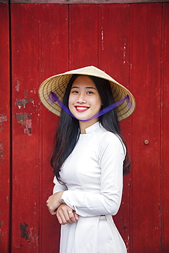 A young Vietnamese woman in traditional dress standing at the Western gateway to the Purple Forbidden City, Hue, Vietnam, Indochina, Southeast Asia, Asia