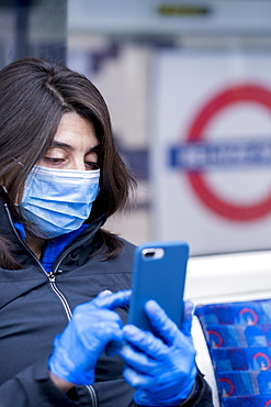 A woman wearing a protective hygiene (pollution) face mask on the London Underground subway system, London, England, United Kingdom, Europe