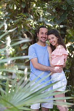 Tropical forest or hotel garden setting and middle-aged couple holding each other and happy together, Bahia, Brazil, South America