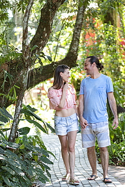 A middle-aged couple happy together on a trail in a tropical forest or hotel garden, Brazil, South America