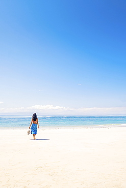 A dark haired woman solo traveller in a wrap holding a sun hat in her hand, on a pristine tropical beach, Indonesia, Southeast Asia, Asia