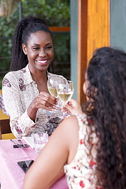 Two female friends, one Black and one Latin, dining together in an al fresco restaurant, Rio de Janeiro, Brazil, South America