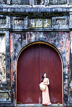 A young Vietnamese woman in a traditional Ao Dai dress and hat standing at the gateway to the Imperial Purple City, Hue, Vietnam, Indochina, Southeast Asia, Asia