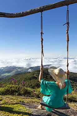 A young woman using a swing over a view of rainforest-covered mountains in the Ibitipoca Reserve, Minas Gerais, Brazil, South America
