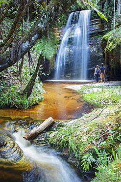 Backpackers enjoying a pristine waterfall and mountain stream in the heart of the South American rainforest, Minas Gerais, Brazil, South America