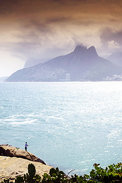 A fisherman on the Arpoador rocks next to Ipanema beach, Rio de Janeiro, Brazil, South America