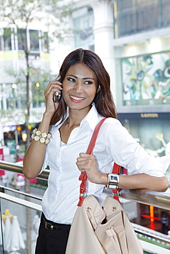 A young Thai woman making a phone call on her cell phone, Thailand, Southeast Asia, Asia