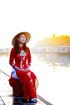 A young Asian woman in a red Ao Dai dress and conical hat smiling and sitting outside next to a river in Hoi An, Vietnam, Indochina, Southeast Asia, Asia