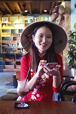 A young Asian woman in a red Ao Dai dress and conical hat smiling and using a mobile phone in a cafe setting, Hoi An, Vietnam, Indochina, Southeast Asia, Asia
