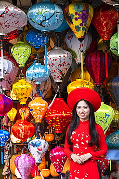 A young woman in traditional Vietnamese clothing standing outside a lantern shop, Hoi An, Vietnam, Indochina, Southeast Asia, Asia