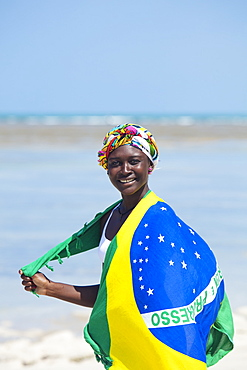 A young black Brazilian woman wearing a head scarf and a wrap showing the national flag, smiling and looking to camera, Brazil, South America