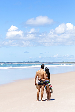 A good-looking Hispanic (Latin) couple on a deserted beach with backs to camera, Brazil, South America