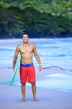 Brazilian male surfer with a Brazilian flag surfboard on a beach in Rio de Janeiro state, Brazil, South America