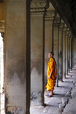 Buddhist monk in a colonnaded corridor in a temple in Angkor Wat, UNESCO World Heritage Site, Siem Reap, Cambodia, Indochina, Southeast Asia, Asia