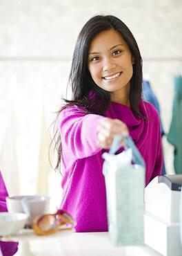 Pacific Islander female sales clerk handing gift bag