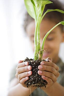Mixed Race girl holding plant