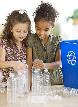 Multi-ethnic girl recycling bottles