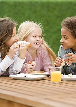 Multi-ethnic girls eating sandwiches