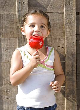 Hispanic girl eating candied apple