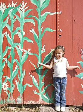 Hispanic girl in front of height marker