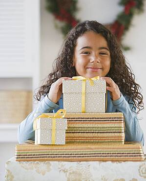 African girl behind stack of gifts
