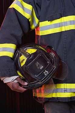 Hispanic male firefighter holding helmet