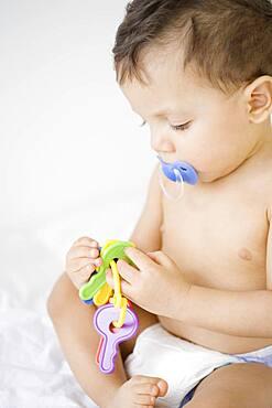 Hispanic baby playing with toy keys
