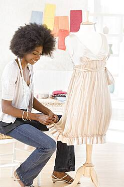 African seamstress working on dress