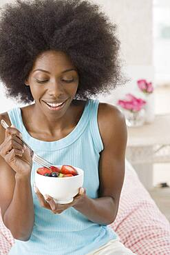African woman eating bowl of fruit