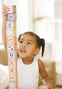 African girl building tower of blocks