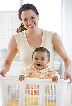 Hispanic mother carrying baby in laundry basket
