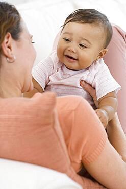 Hispanic baby smiling at mother
