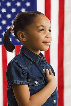 Young girl holding her hand across her heart with American flag in background