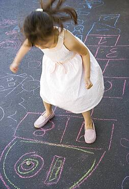 Overhead view of girl playing hopscotch