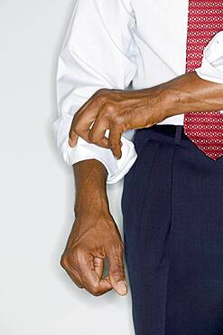 Midsection of businessman rolling up sleeve