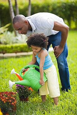 African father and daughter watering flowers