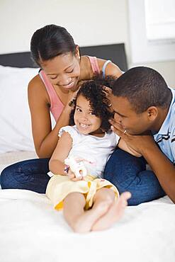 African parents smiling at daughter