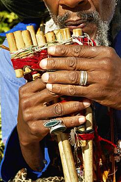 Close up of African man playing pan flute