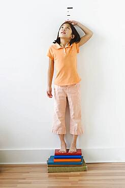 Asian girl standing on books in front of height markers