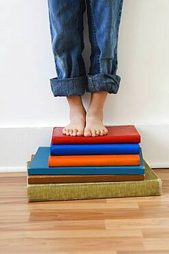 Boy standing on stack of books