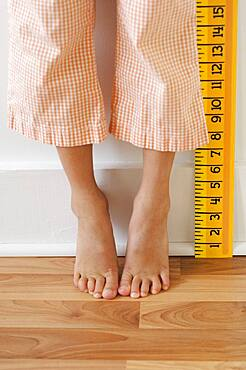 Girl standing on tiptoes next to ruler