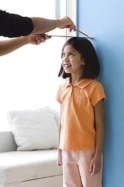 Asian girl having height measured on wall