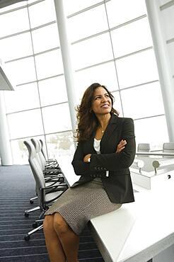 Hispanic businesswoman sitting on edge of table
