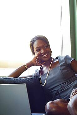 African businesswoman sitting on sofa