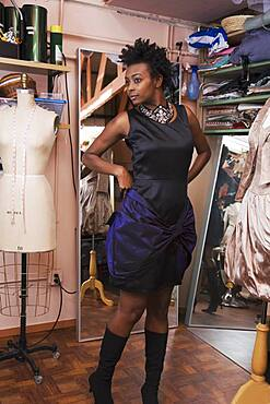 African woman trying on dress at dress making shop