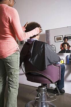African hair stylist cutting Mixed Race man's hair
