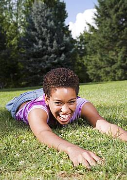 African American woman laying in grass