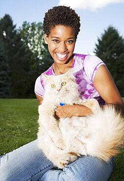 African American woman holding cat