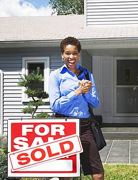 African American woman in front of new house