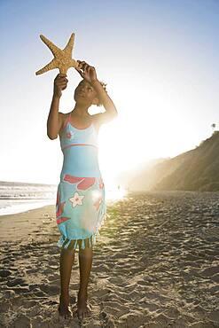 African girl holding starfish